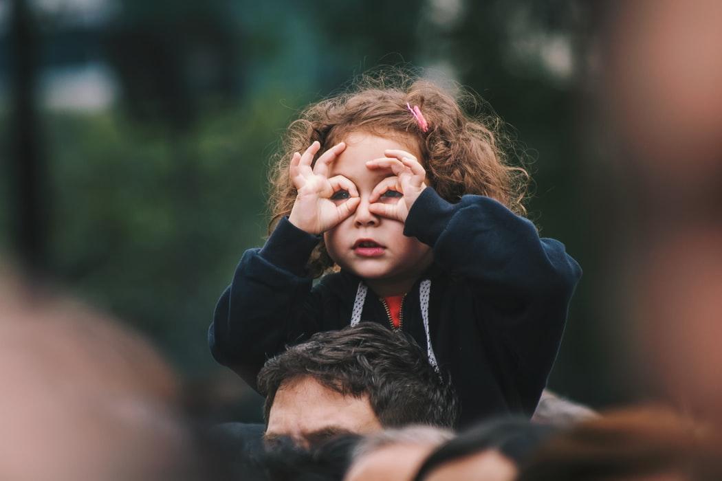Kind op een nek van iemand met een brilletje van haar vingers