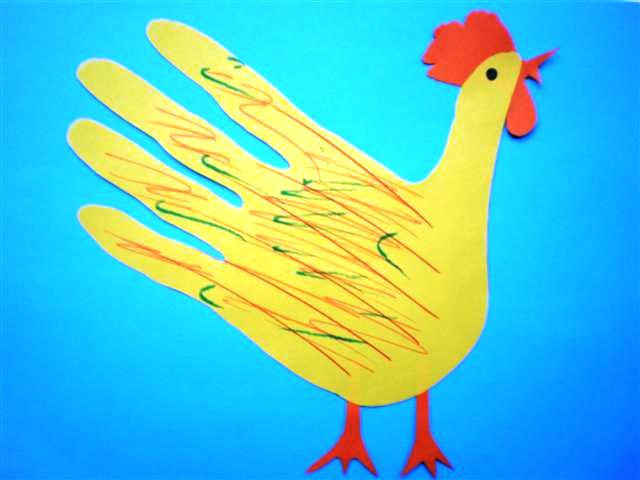 Een gele kip gemaakt van een hand. De achtergrond van de kip is blauw. De poten, lel, snavel en kam zijn rood en het oogje van de kip is zwart. De veren zijn verschillende kleuren; bruin, groen en zwart