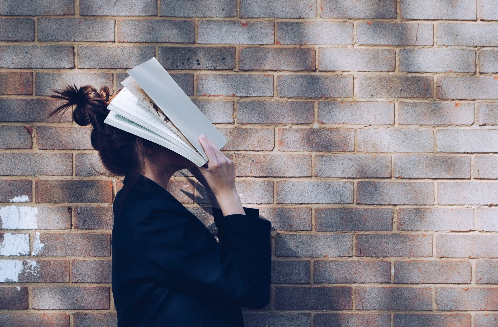 a girl standing in front of wall with papers for her head