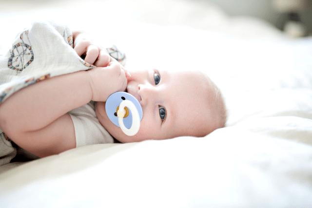 baby ligt op bed met een speen in zijn mond