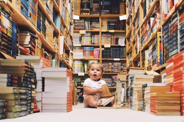 baby zit in een bibliotheek met een stapel boeken voor zich om ontwikkel sprongetjes te stimuleren