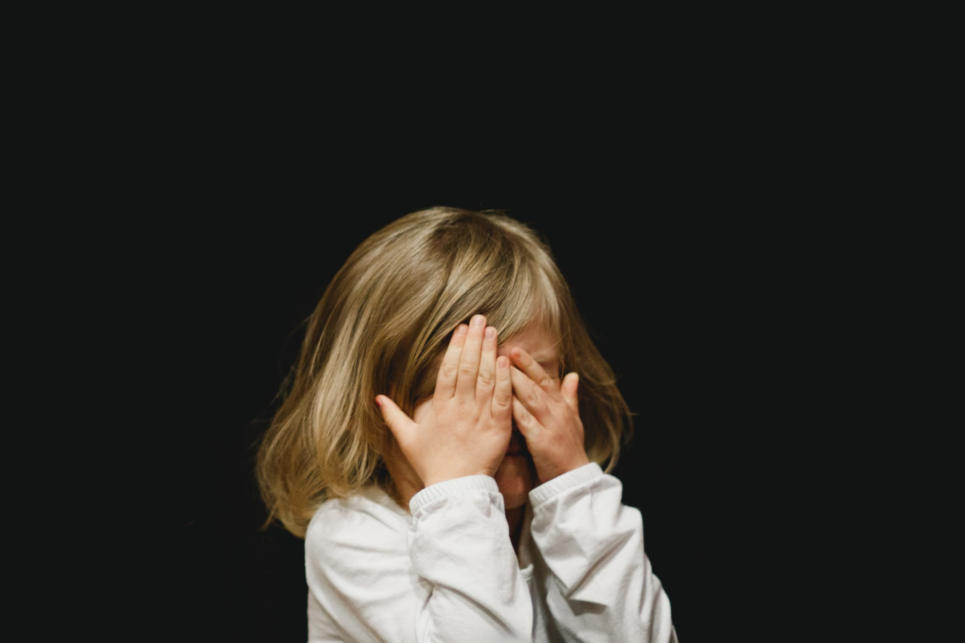 blond girl covering her face with both hands