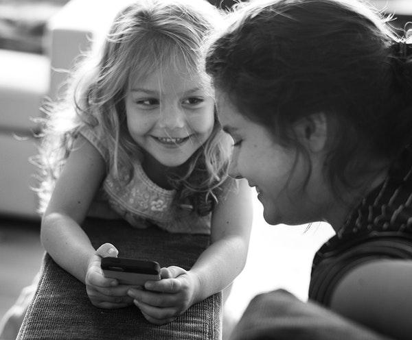 Zwart-wit foto van een blond meisje van ongeveer 6 jaar met een telefoon in haar handen, ze kijkt lachend naar de oppas. En een oppas van ongeveer 21 jaar die lachend naar de telefoon kijkt. Ze hangen op een bankstel