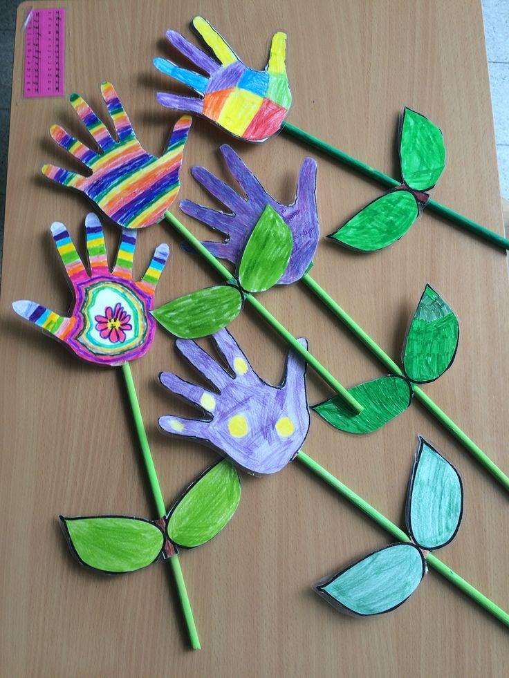 Vijf handbloemen op een tafel. De handen zijn in verschillende kleuren ingekleurd hebben een groene steel met groene blaadjes