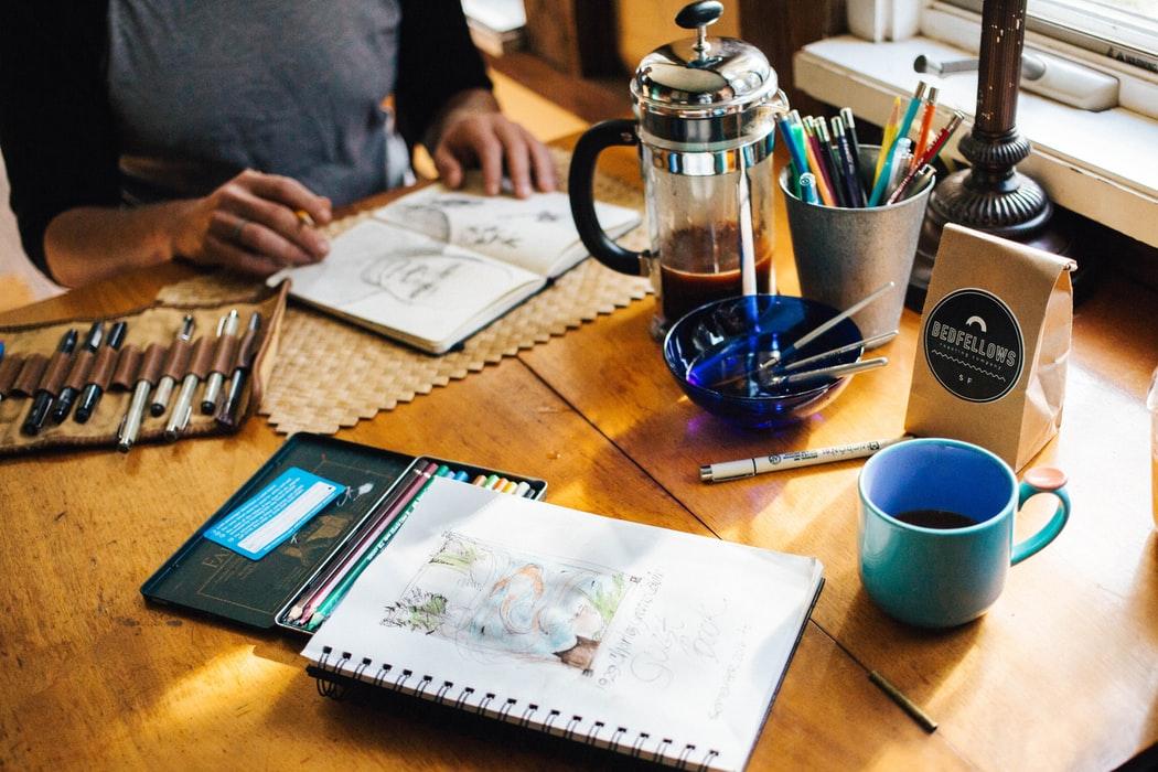 man kijkt naar schetsen aan een tafel met koffie en een pennenpotje