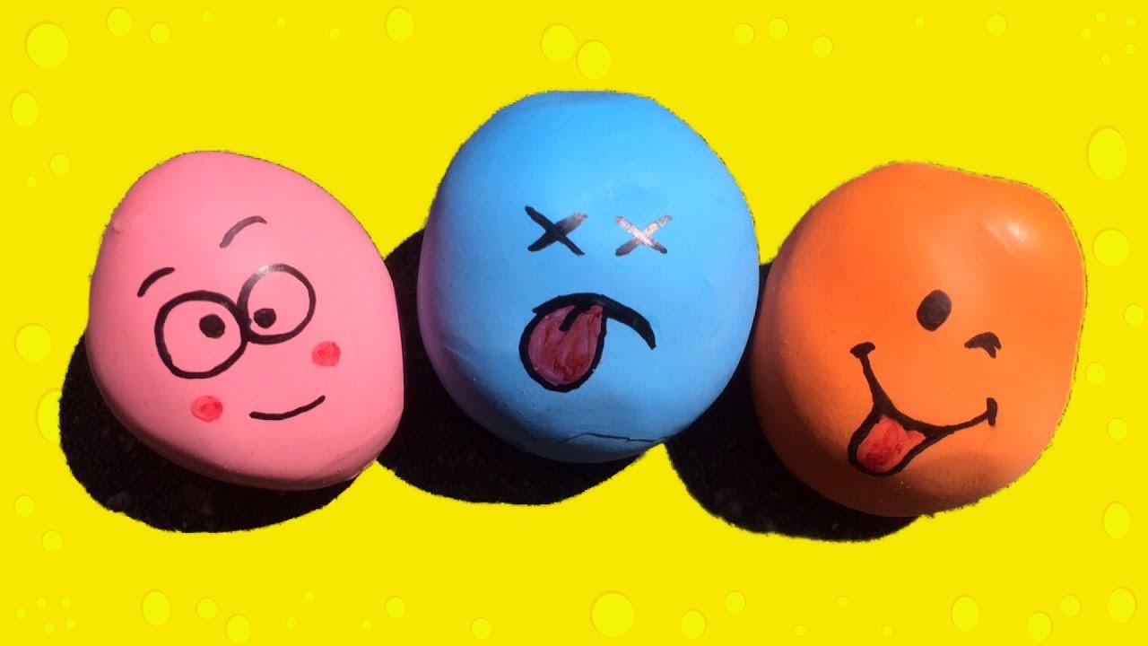 Een roze, blauwe en oranje stressbal met een gezicht gemaakt van ballonnen en zand