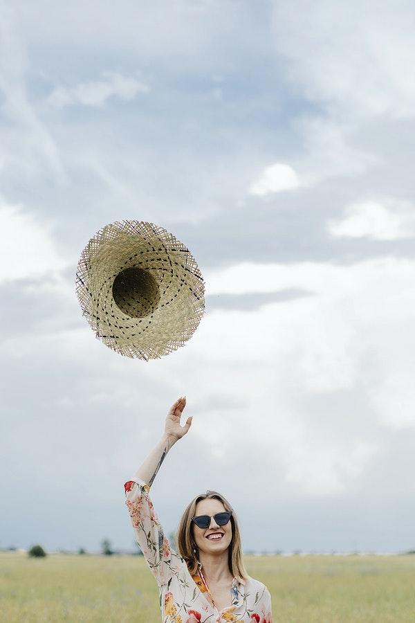 meisje van ongeveer 20 in de velden gooit haar hoed omhoog en draagt een bloemen jurk en zonnebril