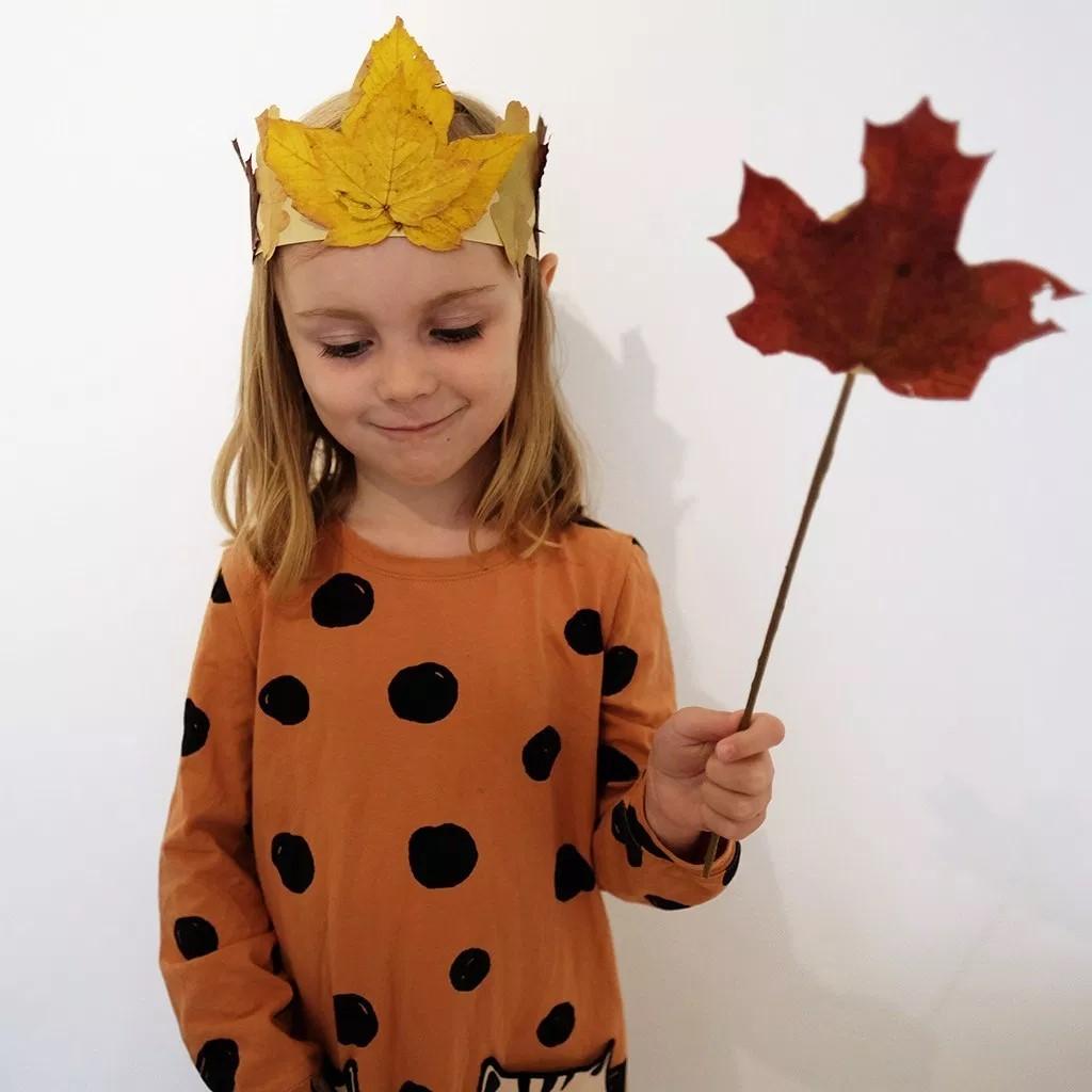 meisje met oranje stippen jurk aan ze heeft een takje met een rood herfst blaadje eraan en een kroon op met een geel herfst blaadje erop het meisje kijkt naar beneden