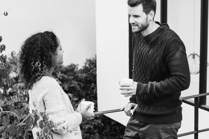 Een man en een jonge vrouw staan in de tuin met een kop thee te praten.