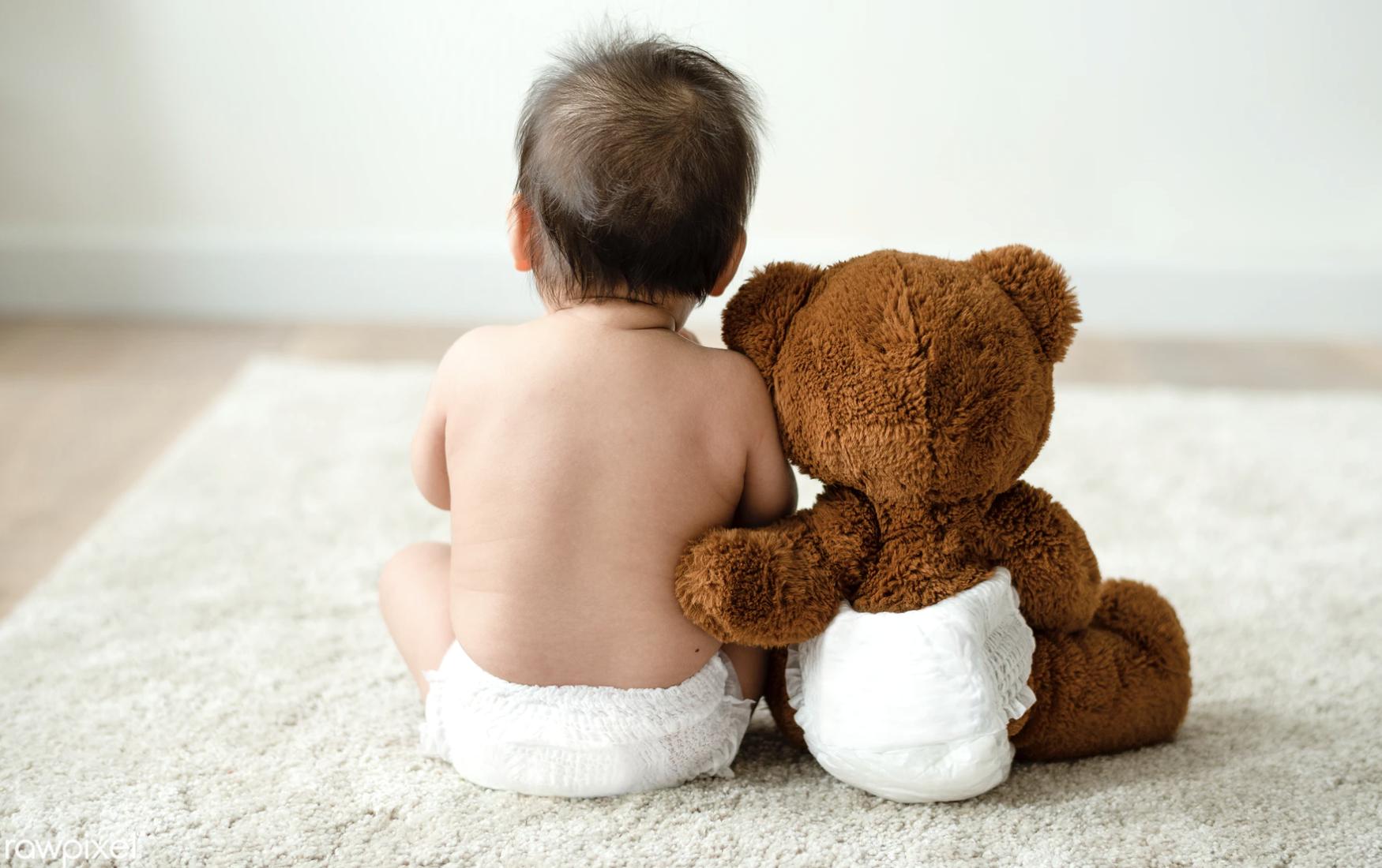 baby en teddybeer zitten naast elkaar te wachten tot de oppas komt.  Wat als je baby huilt? Wat als hij een nieuwe luier nodig heeft? In dit artikel legt moeder iris het uit!