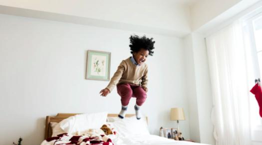 Jongen die helemaal blij is en vrolijk op bed springt
