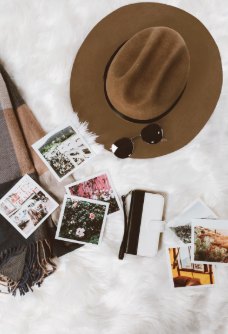 afbeelding van au pair attributen die op reis vertrekt zoals zonnebril, zomerse hoed en fotos.