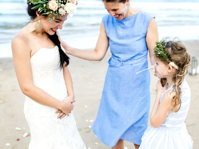 Oppas op een bruiloft staat naast de bruid op het strand en lacht terwijl de bruid met haar dochter speelt op de bruiloft.
