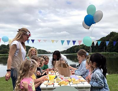 Afbeelding van een bruiloft waarbij de kinderen met de oppas op de bruiloft bezig zijn met een fruitversier workshop. De kinderen zitten aan een tafel van hout met uitzicht over het water en balonnen in groen zilver en blauw.