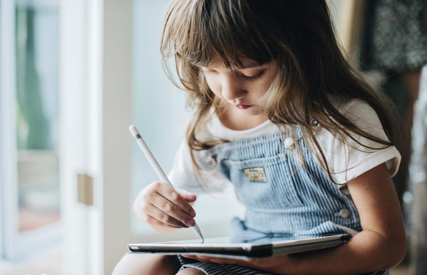 Meisje die in bij het raam op har iPad aan het tekenen is.