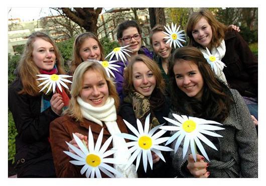 Groep vriendinnen met geknutselde madelief bloem in hun handen