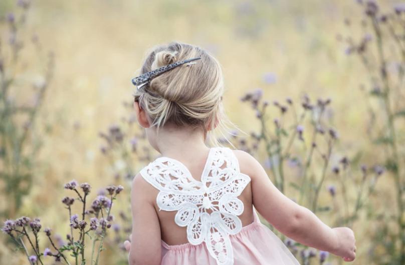 kindje op een bruiloft loopt buiten als activiteit door het veld om bloemen te plukken en hier een bloemenkrans mee te maken samen met de oppas. De oppas wacht bij de andere kinderen die ook bezig zijn om bloemen te verzamelen op de bruiloft.