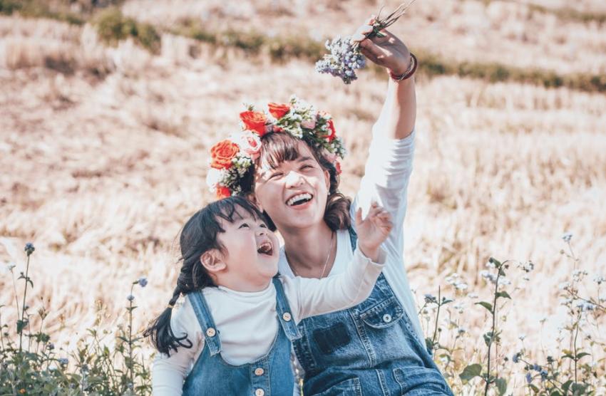 Oppas en kindje op een bruiloft spelen samen en maken een selfie foto van hun bloemenkransen. Ze zitten lekker in het gras en de zon schijnt, een prachtige dag voor een bruiloft. De oppas en de kinderen hebben een superfijne dag met spelletjes buiten doordat het zulk lekker buitenspeel weer is met buiten activiteiten voor de kinderen op de bruiloft.