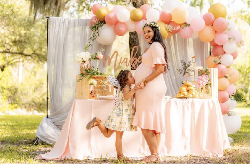 Oppas en kindje staan bij de tafel met knutselspullen op de bruiloft. Alles is roze en oranje en je ziet balonnen op de achtergrond van de oppas.
