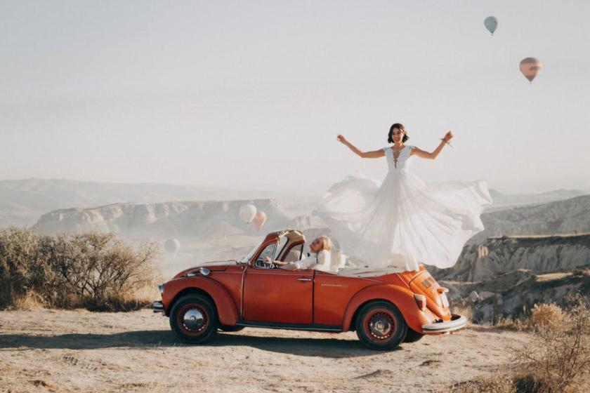 Oppas maakt een foto van de bruid en bruidegom die hun bruiloft  vieren met een foto die de oppas neemt van het stel met luchtbalonnen op de foto. De bruiloft is in de bergen met zon buiten en de bruid heeft een witte jurk aan.