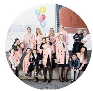 wedding nannies in pink coats and balloons are smiling in the camera together with some children.
