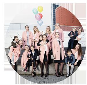 afbeelding van bruiloft wedding nannies in roze jassen die met ballonnen lachend de camera in kijken.