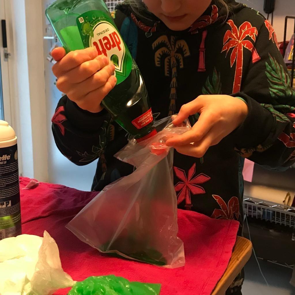 Kind spuit afwasmiddel Dreft in plastic boterhamzakje om zo smurfensnot te maken