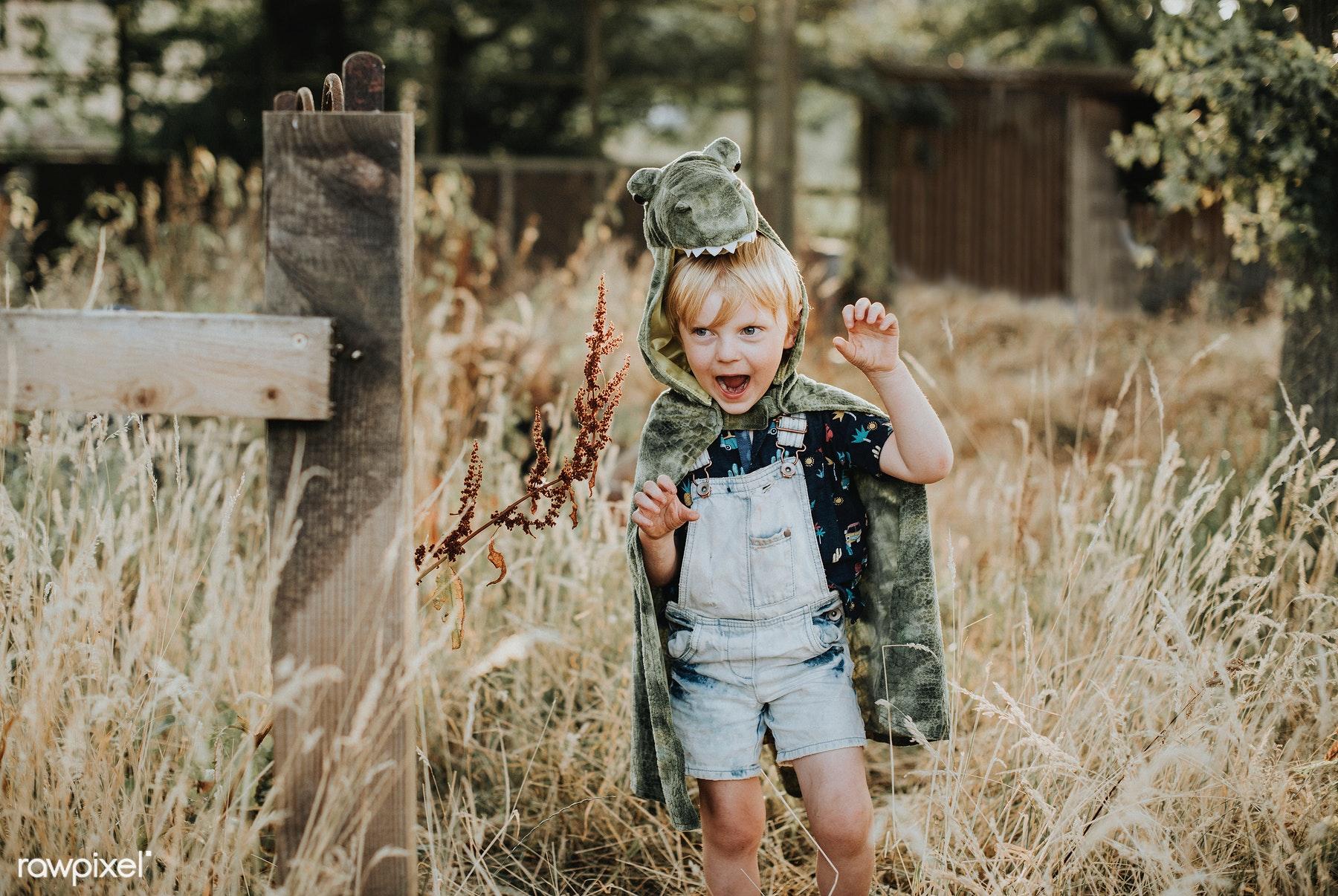 Jongetje buiten in een veld in tuinbroek met een krokodillendeken over zich heen