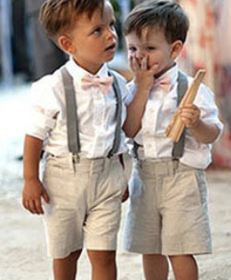 two cute boys in wedding outfit are walking together, the wedding nanny is walking behind them