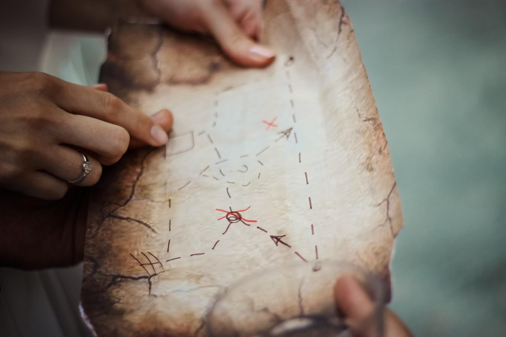 Iemand die met twee handen een schatkaart vasthoudt en op zoek is naar de route die te zien is door de peilen, streepjes en rode kruizen