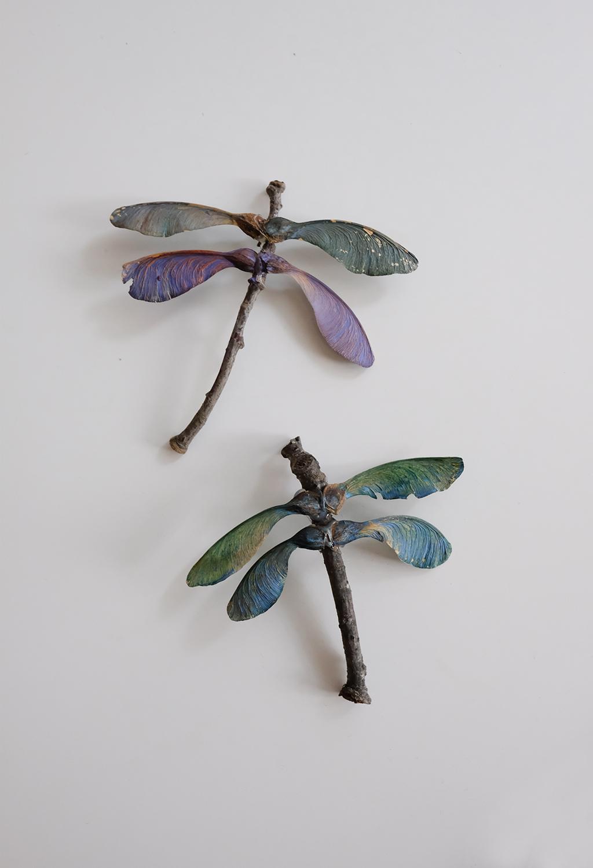 twee libelles gemaakt van takjes en esdoornzaden met de bovenste heeft paarse vleugels en de onderste blauwe vleugels