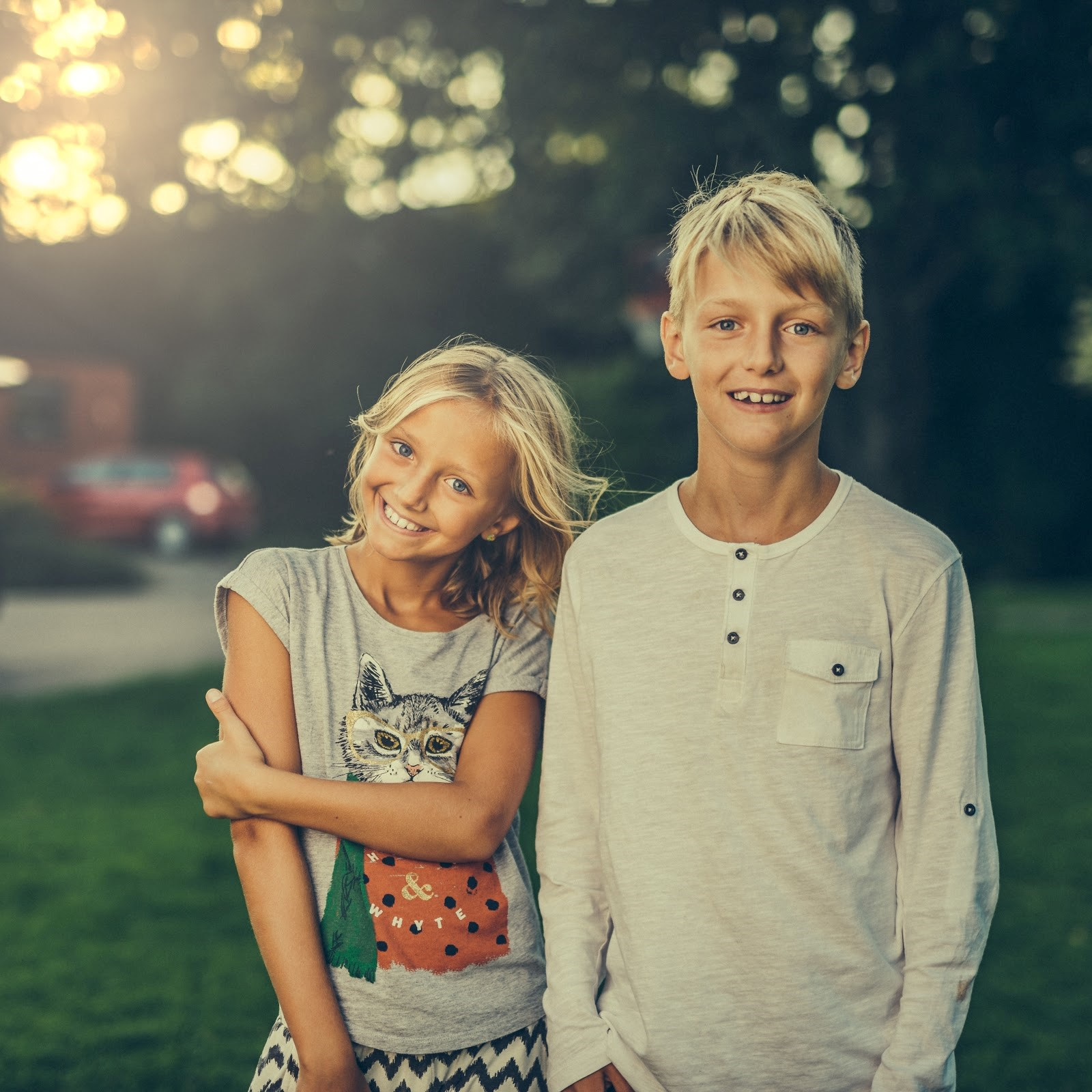 two blond kids next to each other left is the younger sister of the right boy next to her they are in a park smiling to the camera