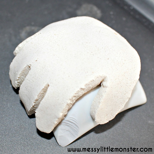 Een wit handje gemaakt van zoutklei. Het handje ligt op een stenen kommetje om er zo voor te zorgen dat het handje rond wordt.