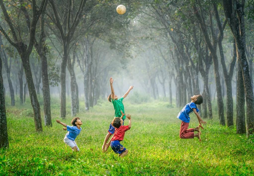 vier kinderen die in het bos naar een bal aan het springen zijn