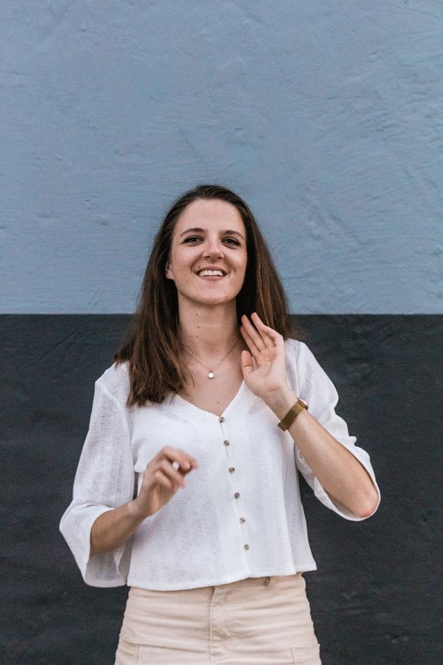 vrolijk meisje met bruin haar kettinkje om wit blousje aan horloge om dat geschikt is om te dragen als oppas