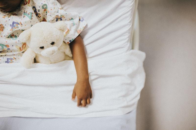Kind in bed met een teddybeer. Je ziet het kind niet, alleen een kindhandje dat de beer vasthoudt.